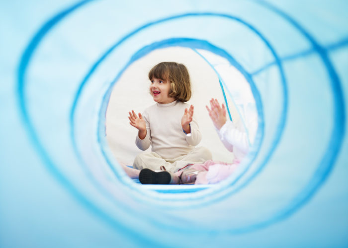 2-3 years old girls viewed from blue toy tunnel, clapping hands and singing. Horizontal shape, Copy space